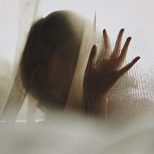 woman leaning on glass window