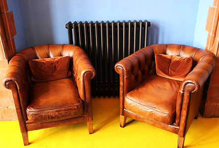two brown leather armchairs inside the room