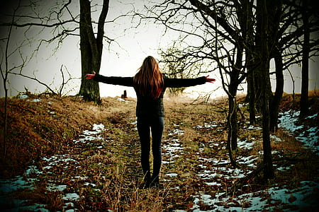 photo of woman standing beside bare tree