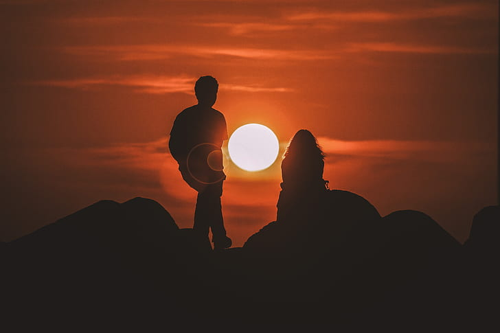 silhouette of man and woman on the rock