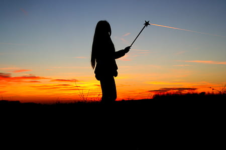 silhouette of woman holding star stick during dawn