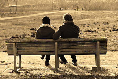 two person sitting on wooden bench