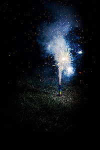 photo of lighted firecracker on ground during night time