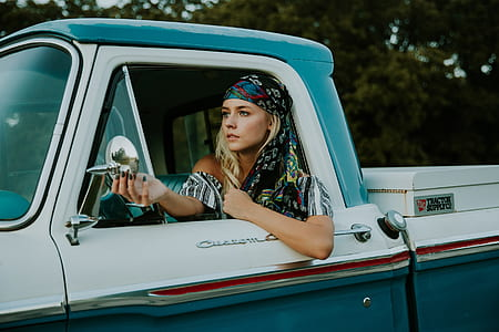 woman in white and grey shirt sitting inside pickup truck while looking mirror during daytime