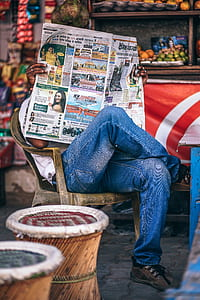 tilt shift lens photography of man wearing blue jeans while holding newspaper