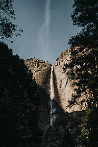gray rock mountains with waterfalls under gray sky at daytime