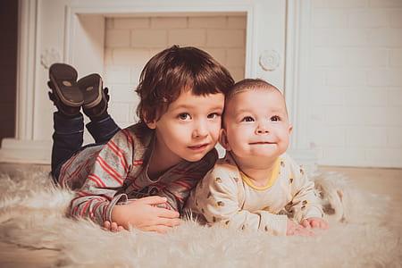 baby on white fleece textile beside a boy wearing grey sweater