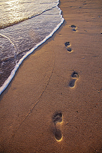 footprints in sand near seawave