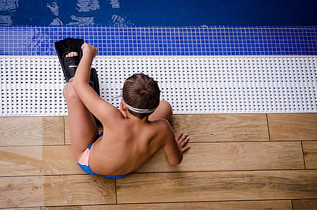 boy wearing black flippers sitting near swimming pool