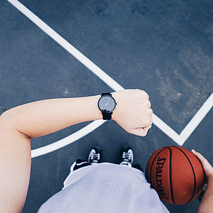 person wearing black analog watch and holding spalding basketball