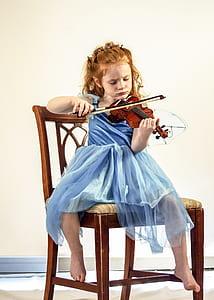 girl wearing blue dress playing violin
