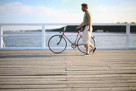 selective focus photography of man holding bicycle on beach deck