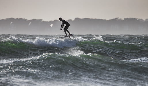 silhouette photo of surfing man