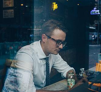 man in white dress shirt sitting inside the restaurant