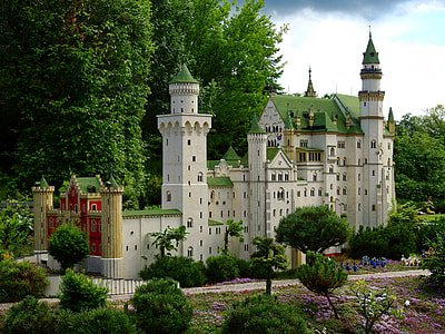 white and green castle surrounded by trees during daytime