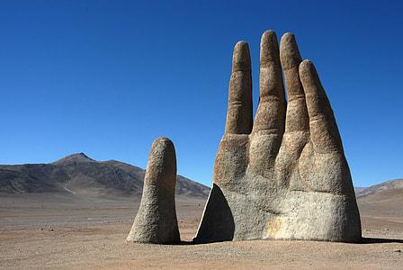 gray concrete human hand statue