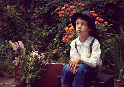 girl wearing white bertha-collar long-sleeved shirt sitting on garden