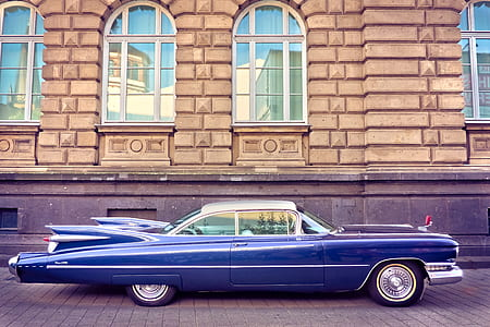 classic blue coupe parked near brown building