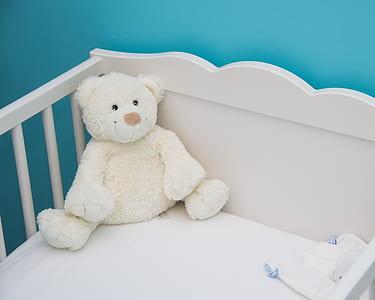 white bear plush toy on white wooden crib