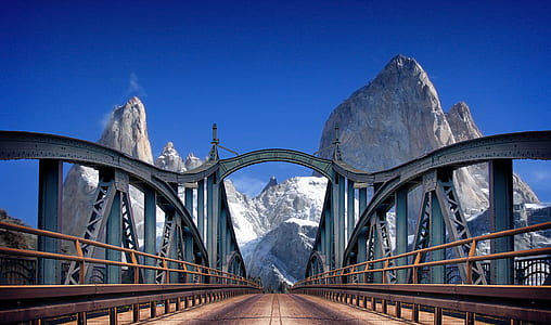 photo of gray metal bridge near mountain