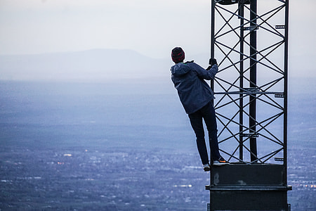 man in blue jacket stands on black tower overlooking city