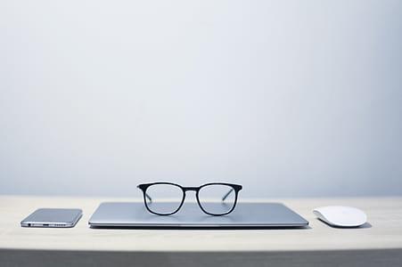 black framed eyeglasses on top of laptop