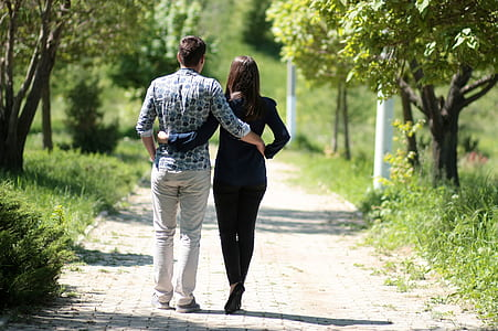 couple holding each others waist while walking on pathway during daytime