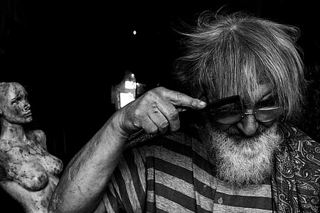 grayscale photo of man combing his hair