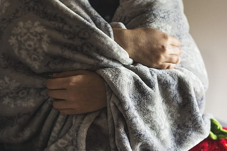 person wrapped in gray fleece blanket