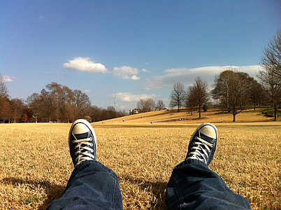 photo of person in black pants and Converse All Star shoes laying on grass
