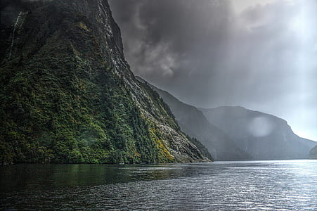 landscape photography of black and green mountain range beside body of water