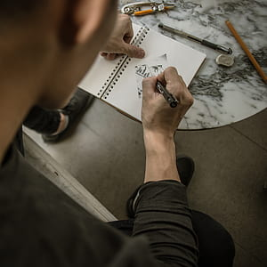 man drawing on notepad in closeup photography