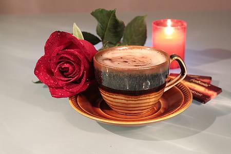 brown ceramic teacup near red rose