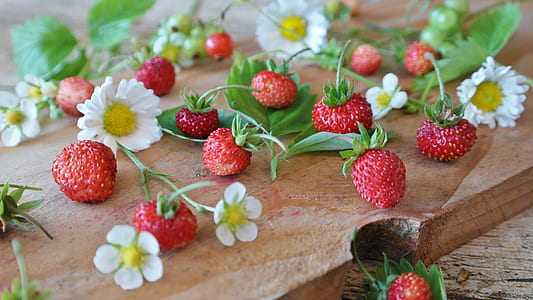 strawberries and white daisy flowers on table