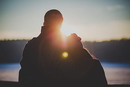 silhouette of couple facing body of water