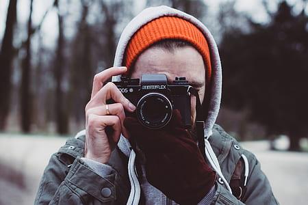 person taking picture using black camera