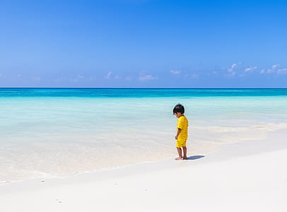 boy wearing yellow top and shorts standing on white sand during daytime