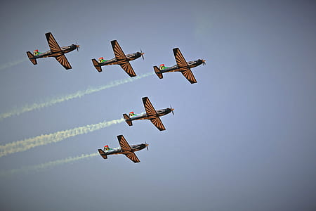 low angle of five black-and-brown planes making smoke trail