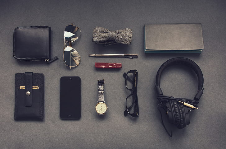 black headphones, black framed eyeglasses, black smartphone, black leather card wallet