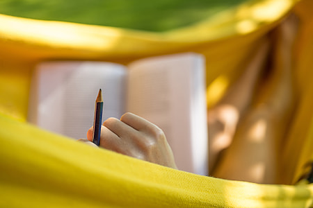 Woman studying and reading with pencil in garden