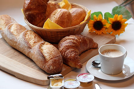 french bread, croissant, butter, and cup of coffee on brown wooden table