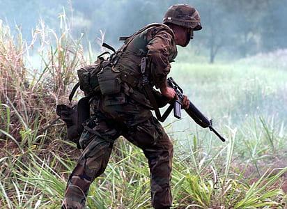 army walking along green grass