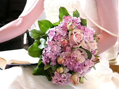woman holding pink and purple petaled flowers bouquet
