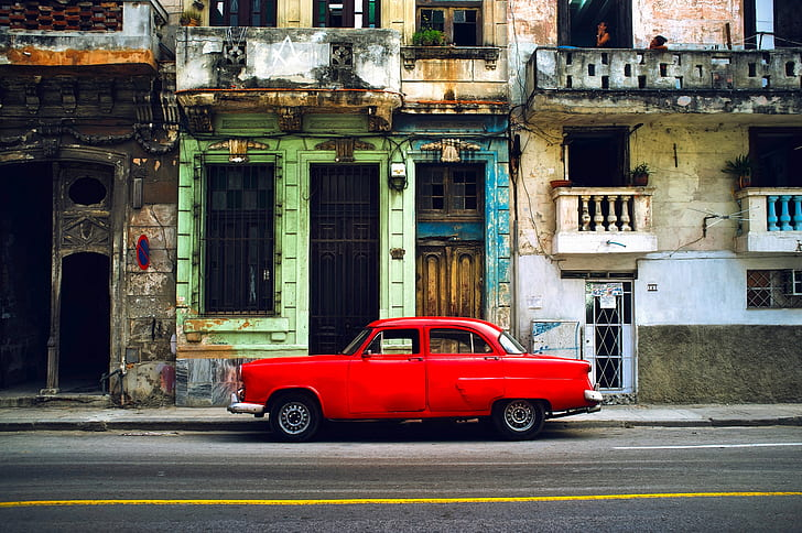 classic red coupe beside gray concrete building during daytime