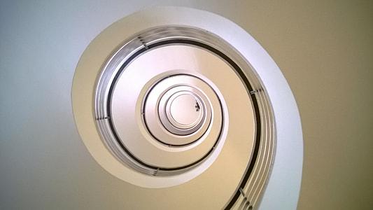 bottom view of white concrete spiral staircase