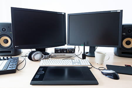 two black flat screen computer monitor on white table