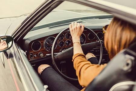 brown haired woman sitting inside car while holding steering wheel