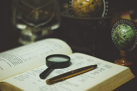 black magnifying glass on white book