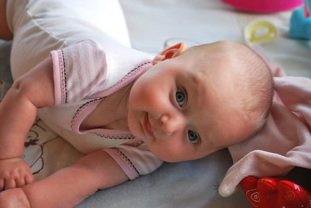 closeup photo of baby wearing white top on blue surface