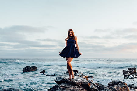woman standing on rock near body of water during daytime